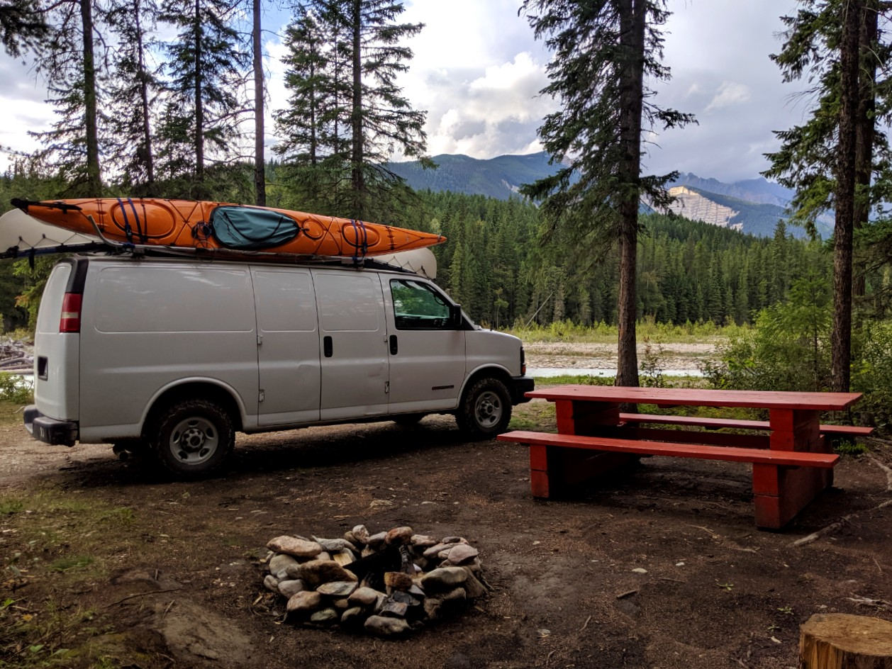 White van parked next to red picnic table at free British Columbia campsite with views of mountains behind