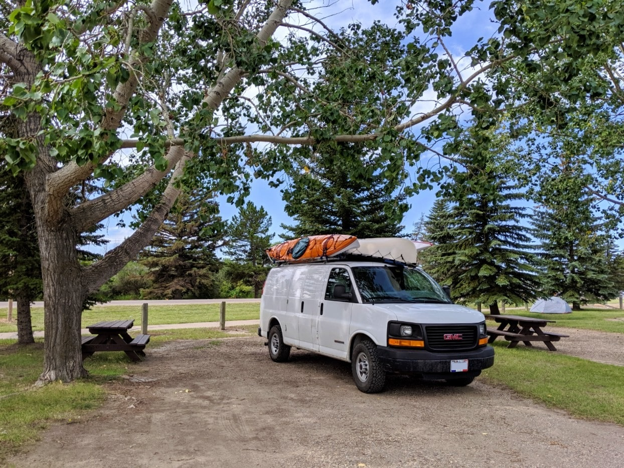 White van parked next to picnic table at free municipal campground in Alberta