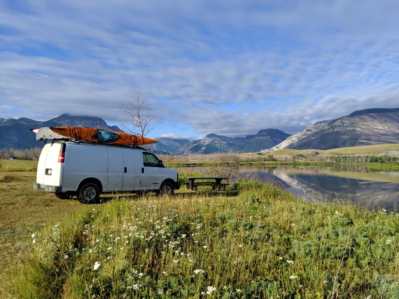White van parked next to river with mountains in background