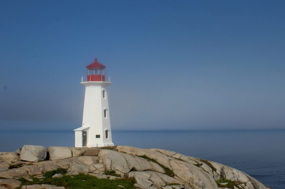The iconic red and white lighthouse at Peggy's Cove, looking out to the ocean from granite rocks