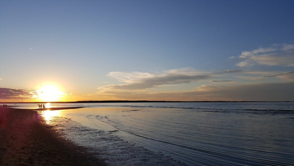 Sunset at sandy beach with calm waves