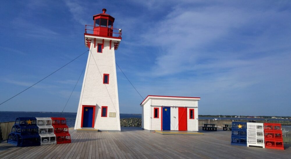 Shippagan lighthouse with Acadian flags and painted lobster pots