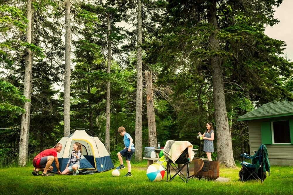 Family around campsite (with tent, camp chairs and beach ball) in Cape Breton Highlands National Park campground