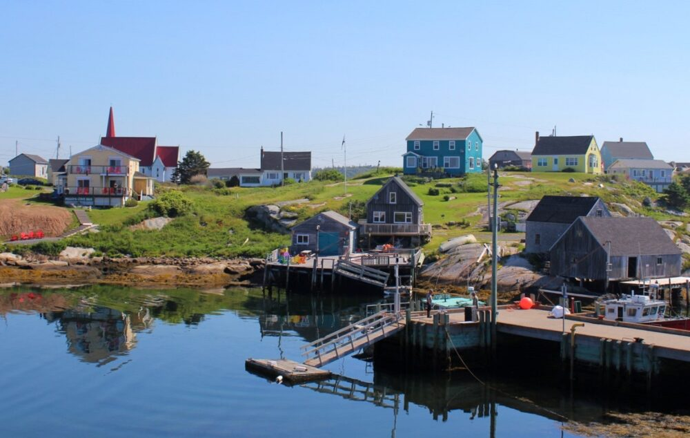 Looking back on a Nova Scotia fishing village with brightly coloured houses dotted on hill near wharf