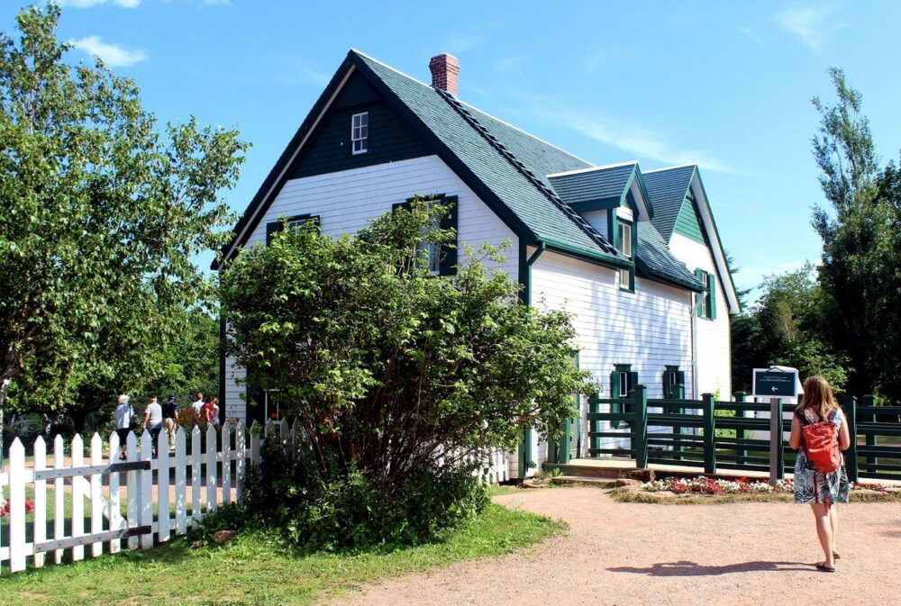 Gemma walking towards the two story PEI farmhouse that inspired Anne of Green Gables