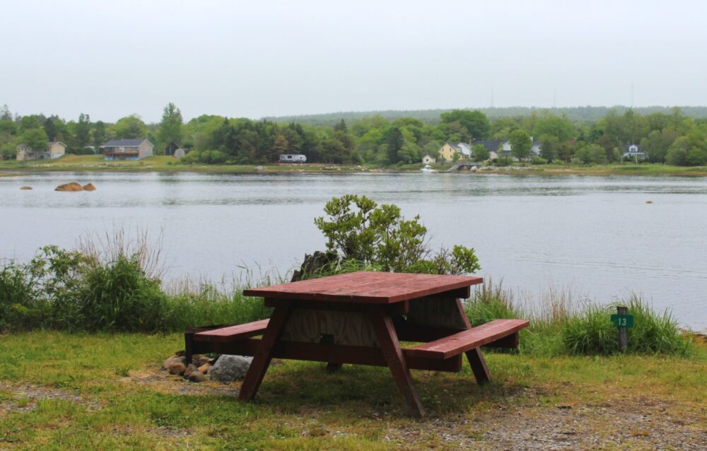 Picnic table and firepit in front of calm water with houses visible on the other side
