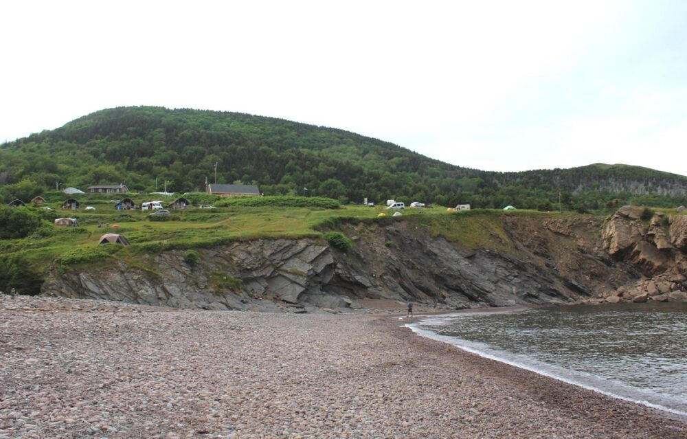 Pebble beach and ocean with campground perched on grassy cliff behind