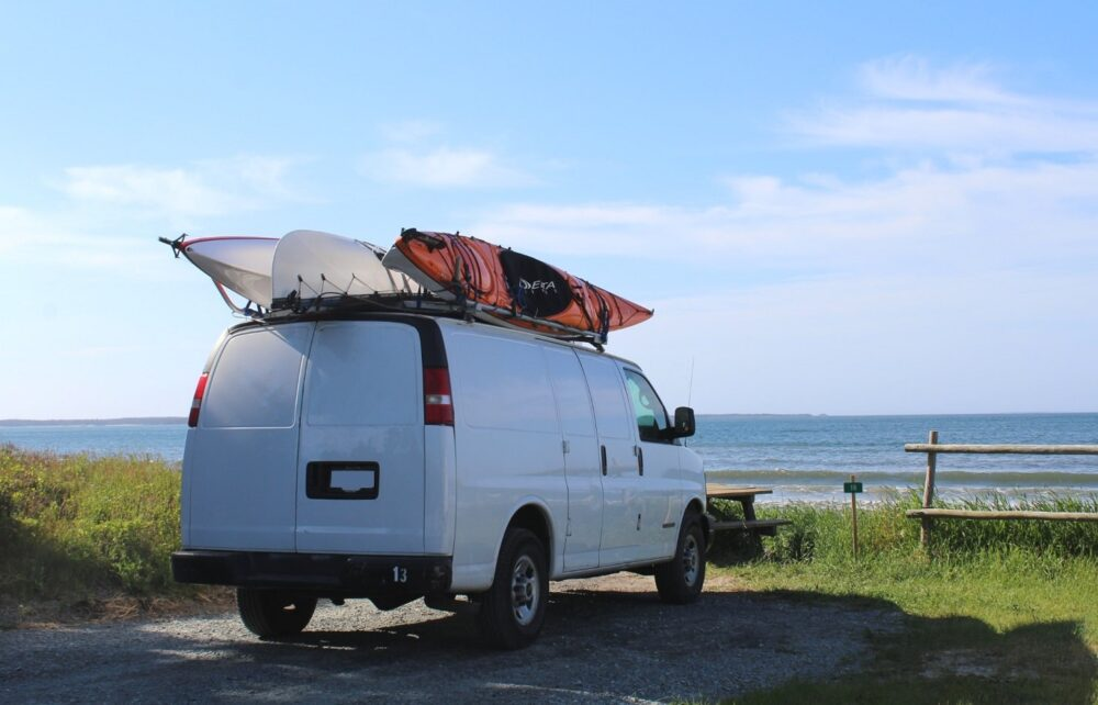 White van parked in camping spot in front of beach, ocean seen beyond