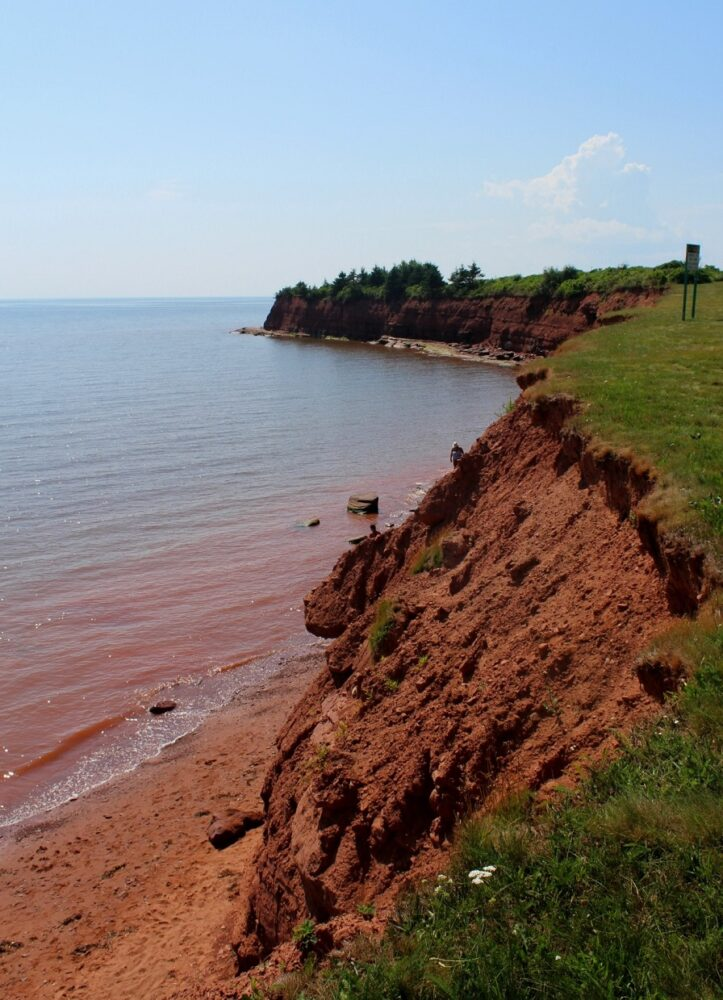 Red cliffs with narrow red sand beach at bottom