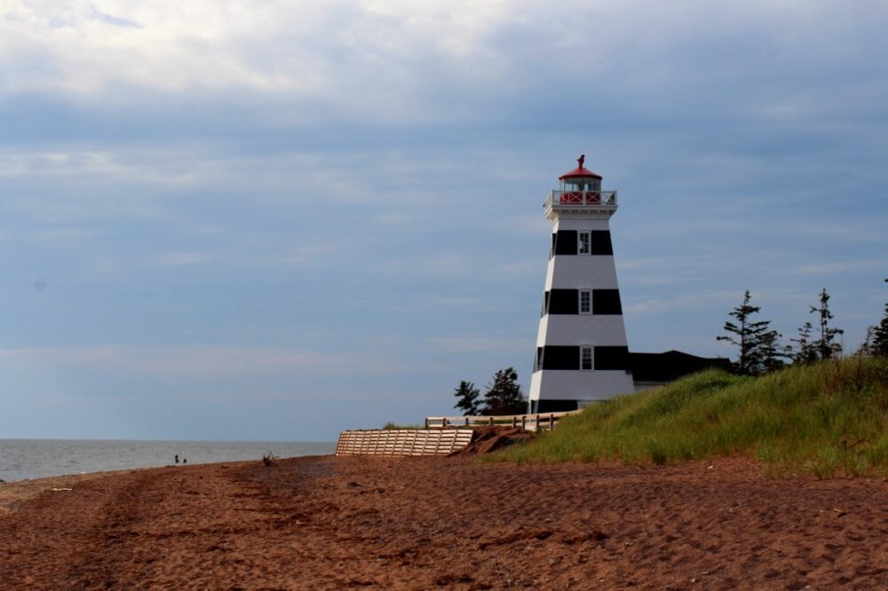 White and black striped lighthouse looking out over Cedar Dunes red sand beach