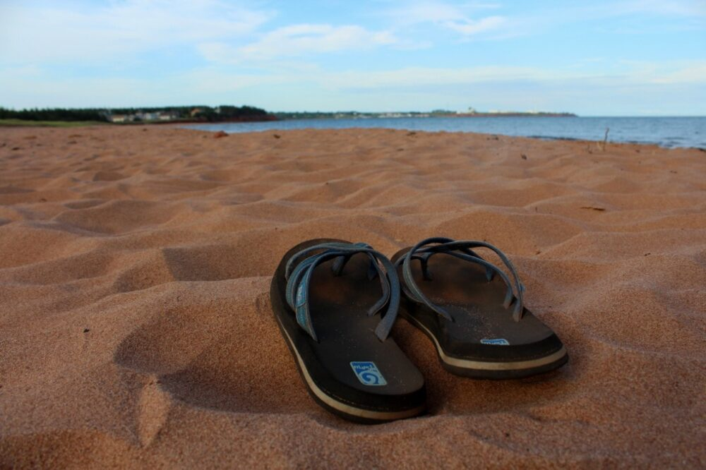 Flipflops on beach with light terracotta sand - Little Harbour Beach, PEI