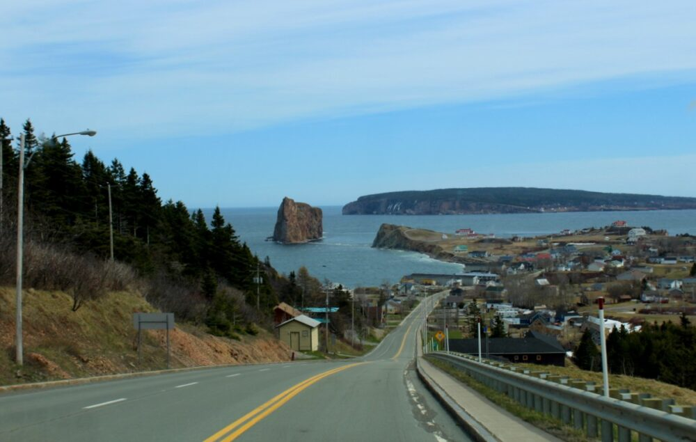 Driving into Perce, with town on right and dramatic Perce rock formation on left