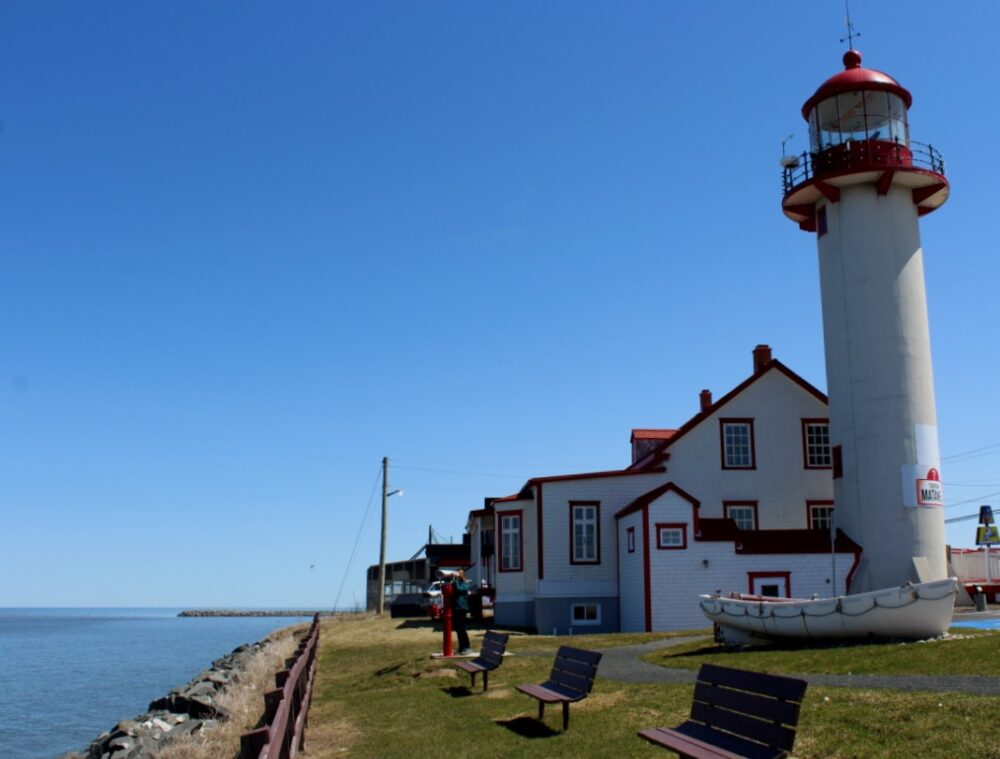White and red lighthouse building in Matane with coastline