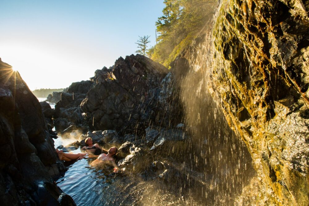 Two people lounging in the natural hot pools of Hot Springs Cove near Tofino. Photographer Jeremy Koreski