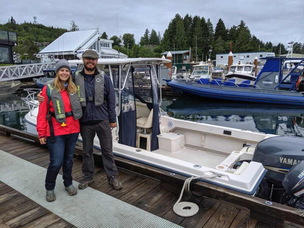 Gemma and JR in front of small boat at Tofino Resort and Marina