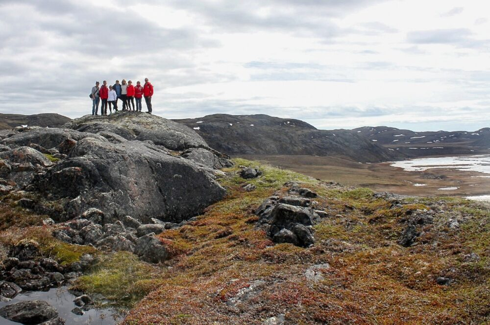 Group of hikers perched on rock with tundra landscape, near Iqaluit, Nunavut