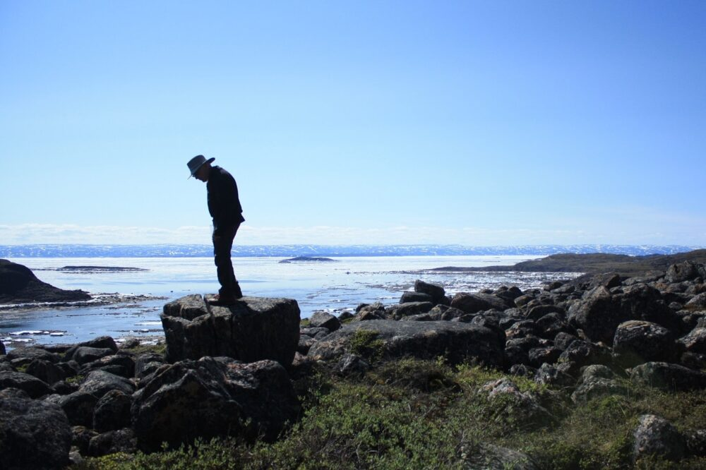 Man standing on rock at Iqaluit coastline in Nunavut, Canada