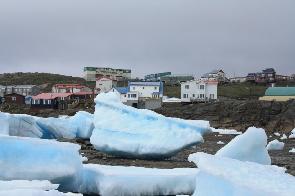 Icebergs in front of colorful houses - one of the unique sights to see on a visit to Iqaluit, Nunavut