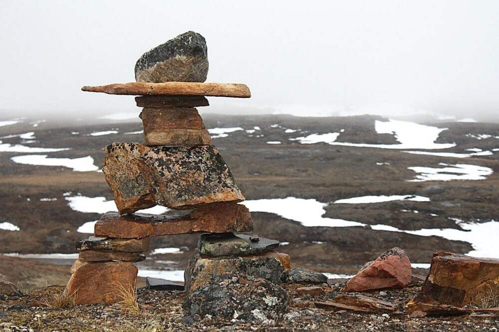 Inukshuk in front of patches of snow in Iqaluit, Nunavut