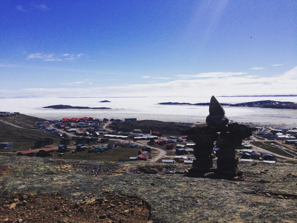 Inukshuk rock stastue in front of township of Iqaluit, Nunavut