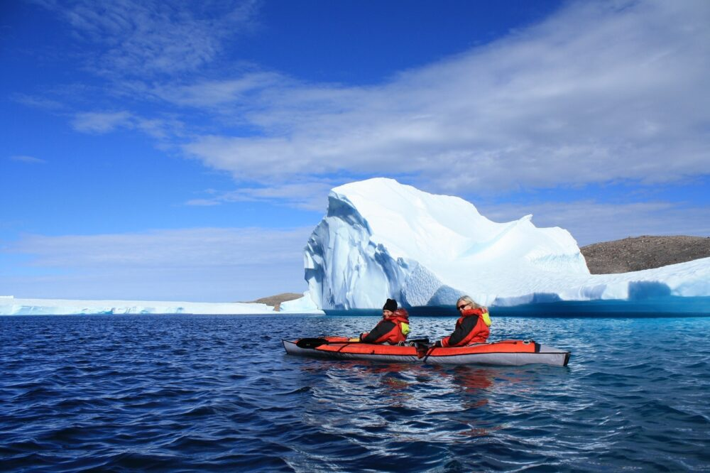 Two paddlers in a red kayak, with huge iceberg behind - near Iqaluit, Nunavut