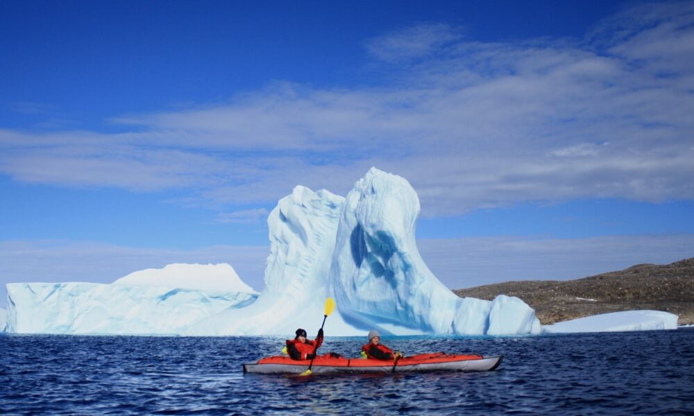 Red kayak with two paddles passing an iceberg near Iqaluit, Nunavut