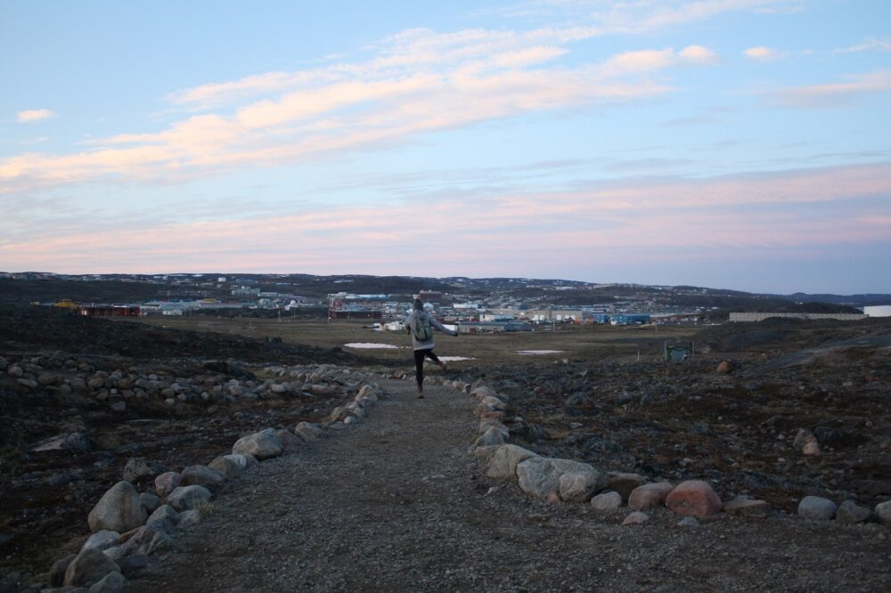 Walking path towards township of Iqaluit, with person walking