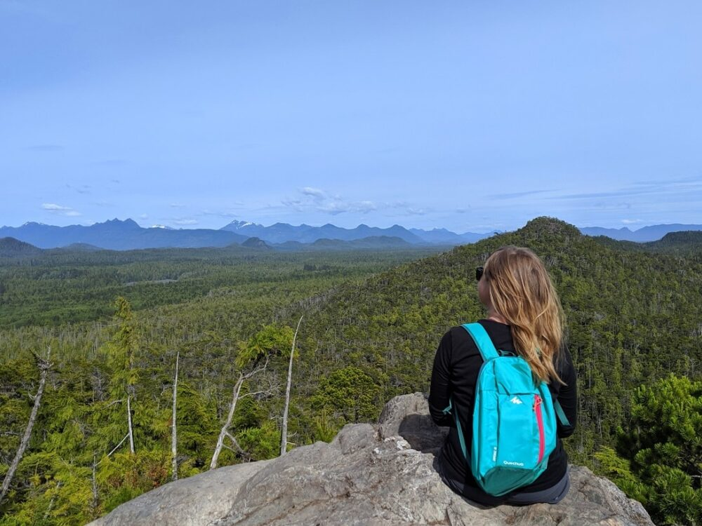 Gemma sat on rock looking out at mountainous views from the top of the Cox Bay Lookout hike in Tofino