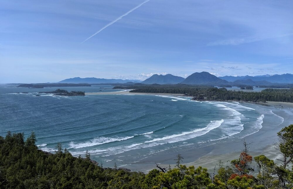 Rolling ocean waves approaching sandy beach, with islands and mountains in background