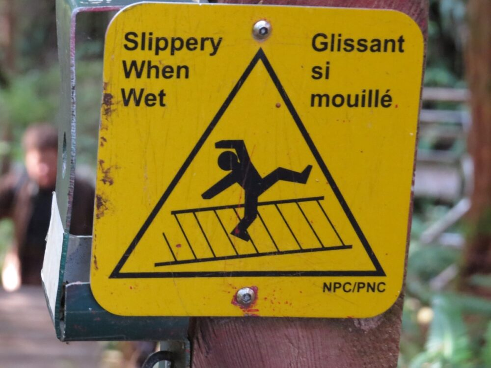 Yellow 'Slippery When Wet' sign with cartoon falling man