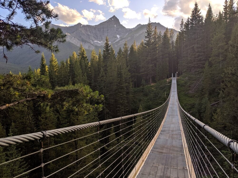 Suspension bridge leading from camera with mountainous backdrop