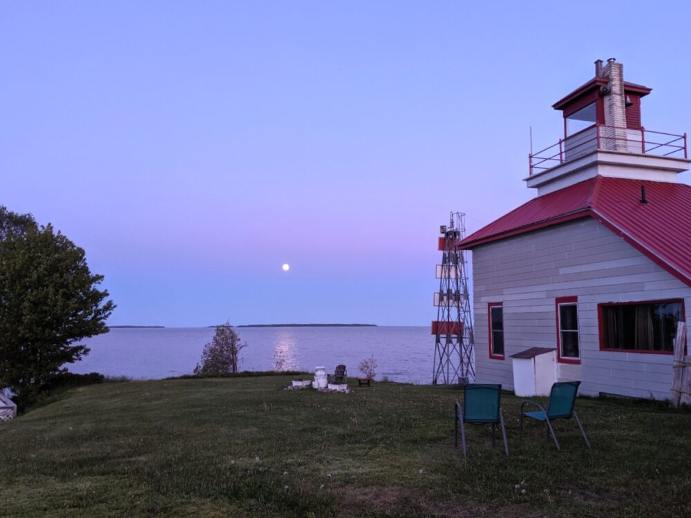 White and red lighthouse perched overlooking Lake Huron