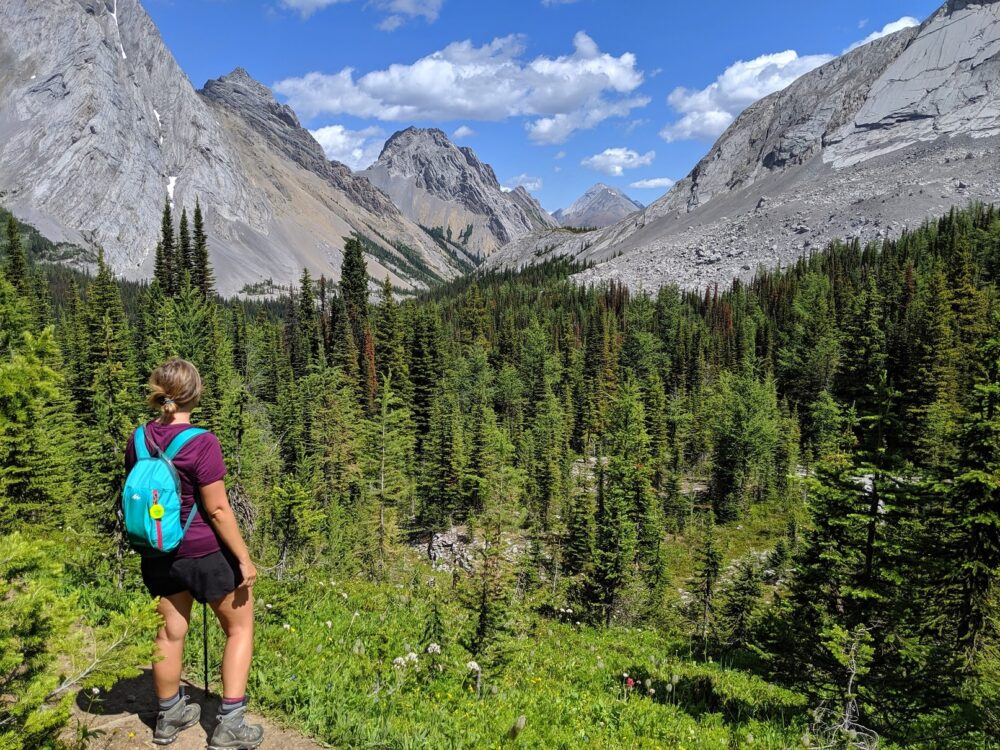Gemma in front of a range of mountains oh the Burstall Pass trail, an example of amazing Kananaskis Valley hiking