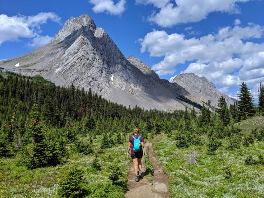The Burstall Pass trail is one of the most rewarding Kananaskis Valley hikes - here, Gemma is hiking underneath Mount Birdwood