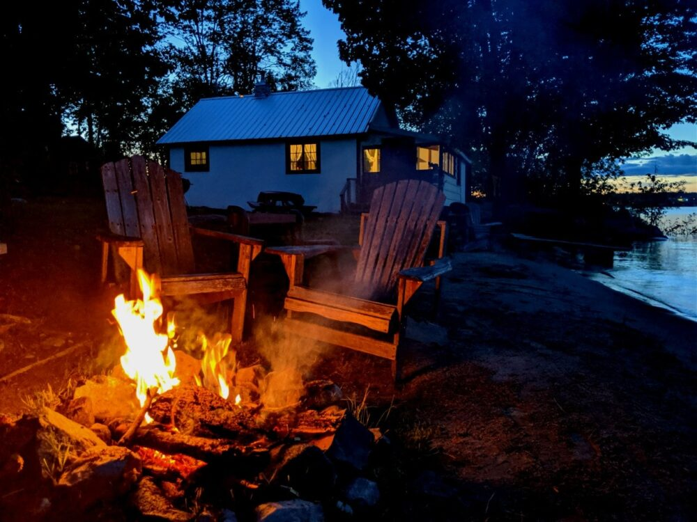 Two Adirondack chairs in front of a campfire at Bruce Bay Cottages, with a cottage behind