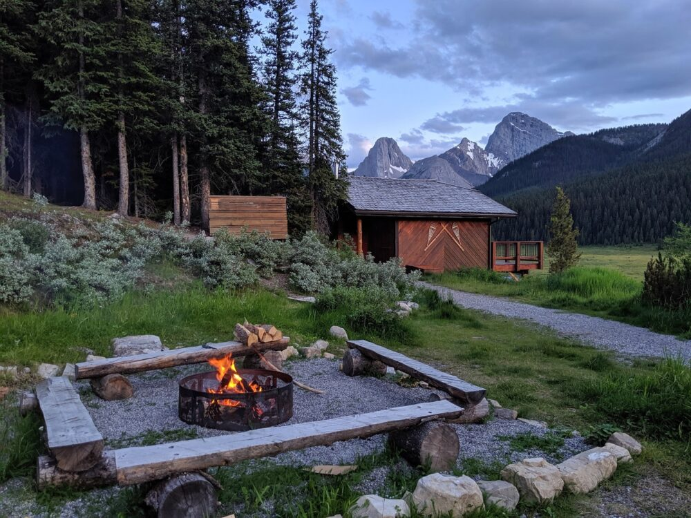 Wooden bench sits set around lit campfire at Mount Engadine Lodge with cabin and mountains in background