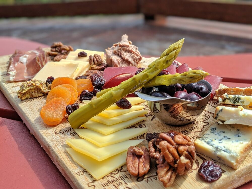 Afternoon tea charcuterie board at Mount Engadine Lodge - three types of cheese, dried meat and cheese, nuts, olives and pickled aparagus