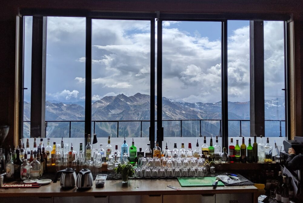 Restaurant bar backed on to large windows, overlooking mountain views