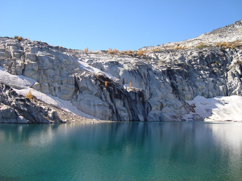 Bright glacial lake surrounded by cliffs and larch trees, in the Enchantments