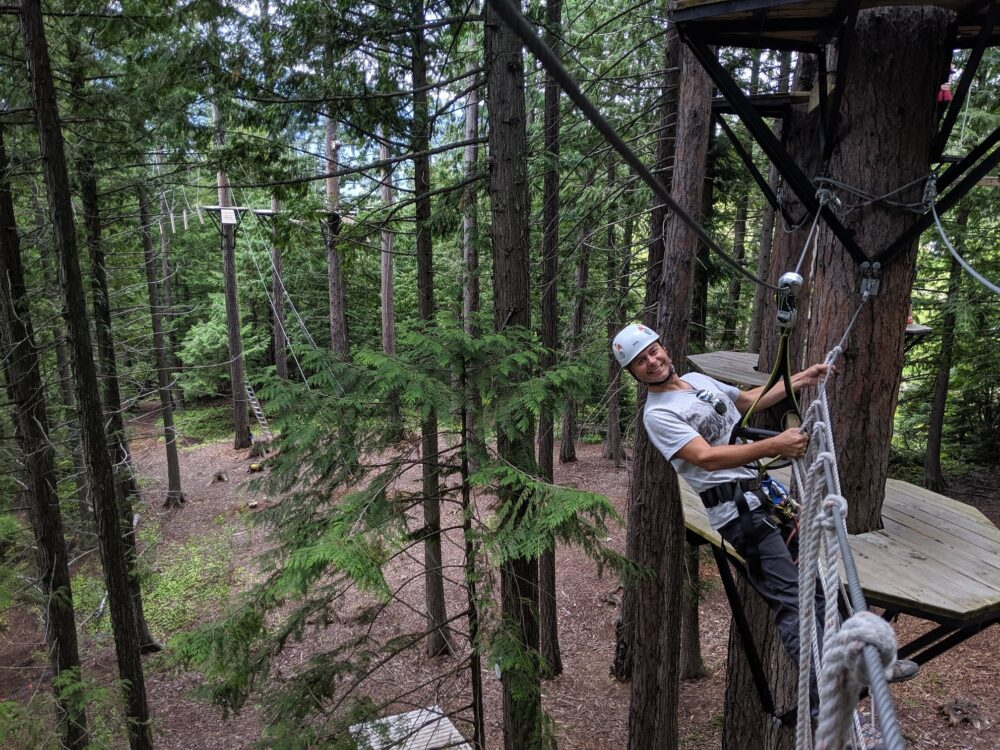JR hanging from rope wall on Fernie aerial park course, Fernie Alpine Resort