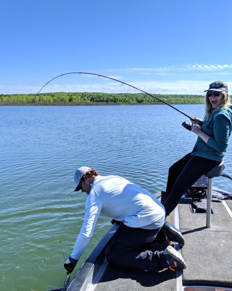 Lindsay looking excited about a northern pike on a her line while Adam reaches into the water to unhook it