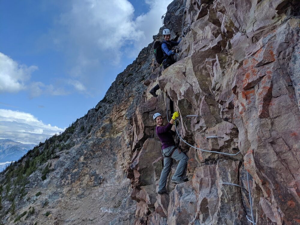 Gemma climbing steel hand and feet holds on the Kicking Horse Via Ferrata