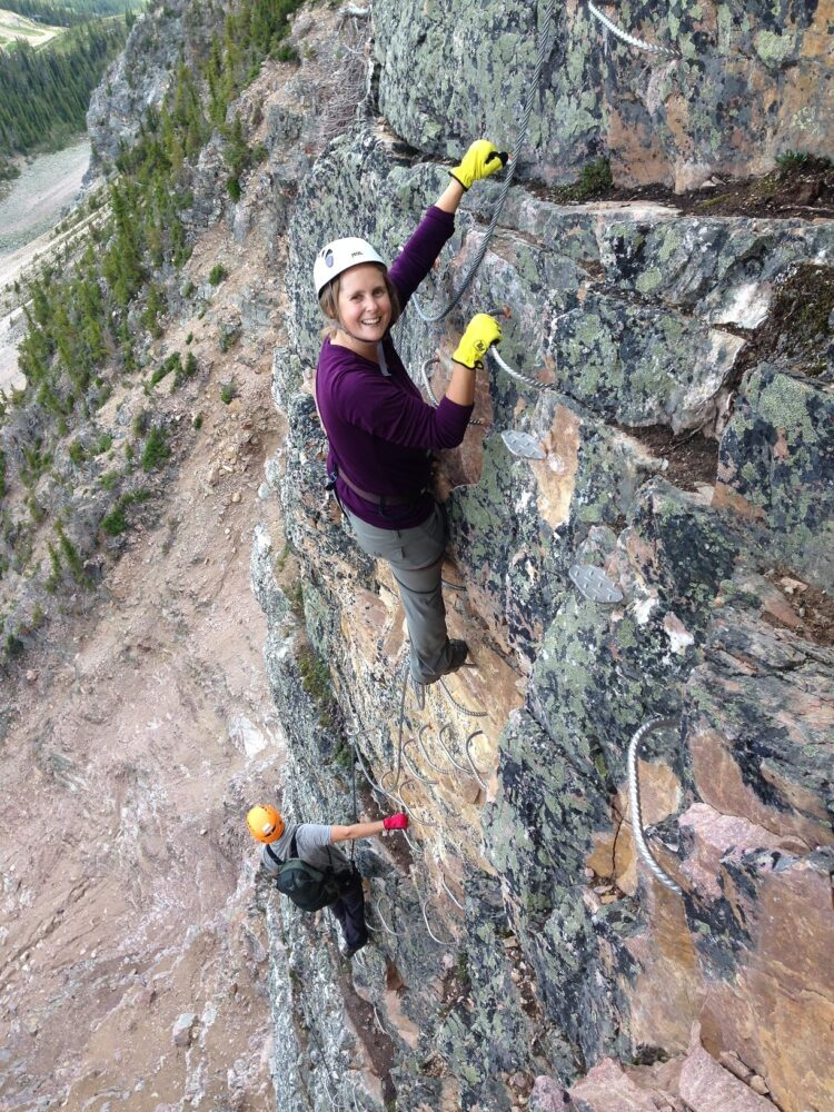 Gemma climbing vertically on the Via Ferrata with JR looks at the views