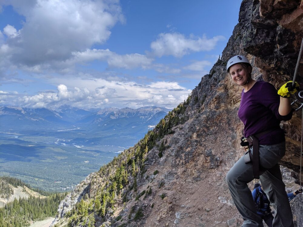 Gemma with back to rock wall on the Via Ferrata, with views of valley and mountains beyond