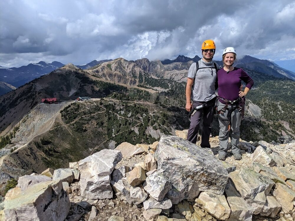 Gemma and JR standing at rocky peak with views of Kicking Horse restaurant and gondola behind