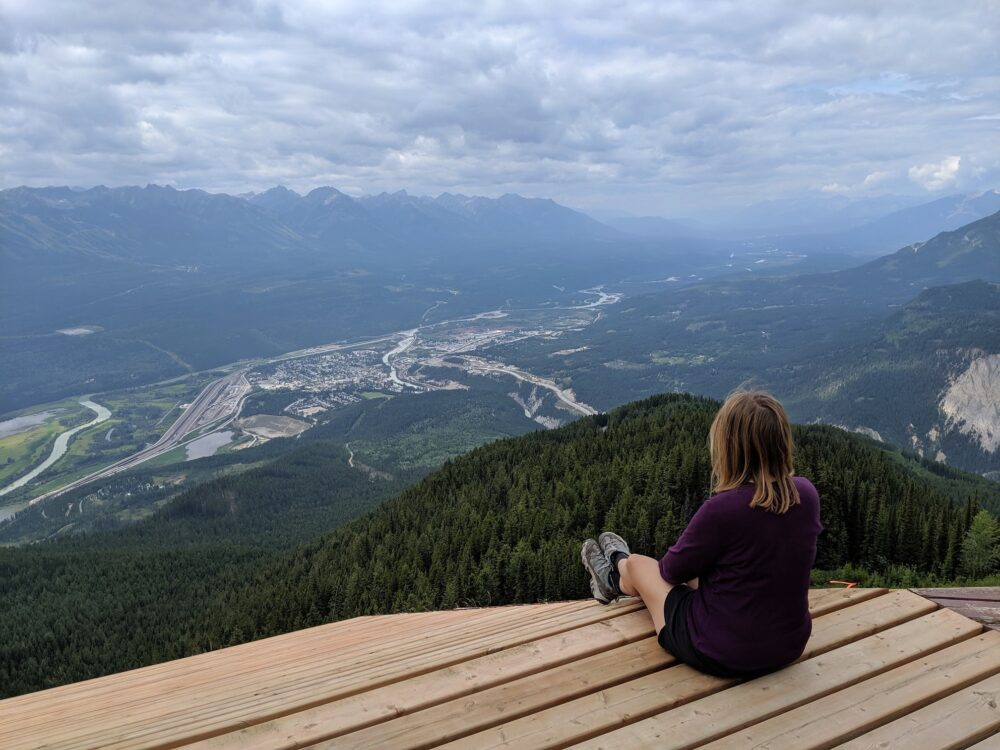 Gemma sitting on wooden platform overlooking town of Golden and mountains