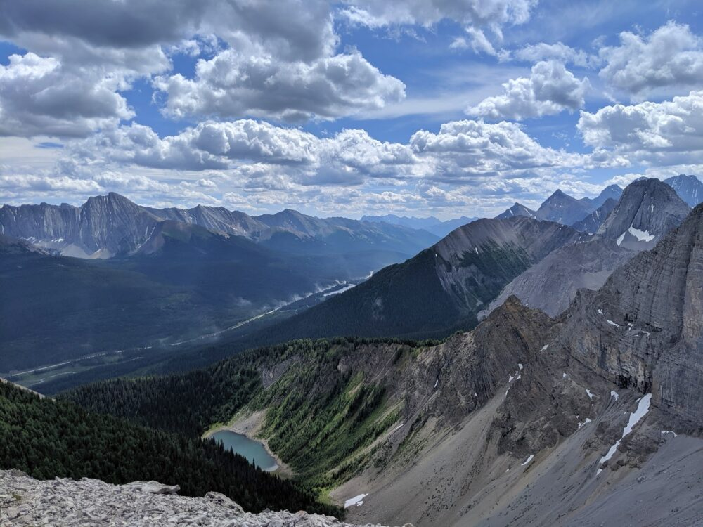 Sloping mountains, highway and a lake on the Tent Ridge trail, one of the best hikes in the Kananaskis Valley