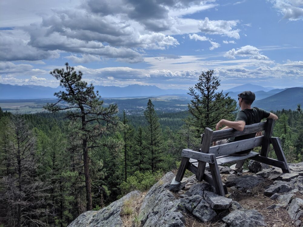 JR sat on bench overlooking mountain and valley views in the Kimberley Nature Park, BC