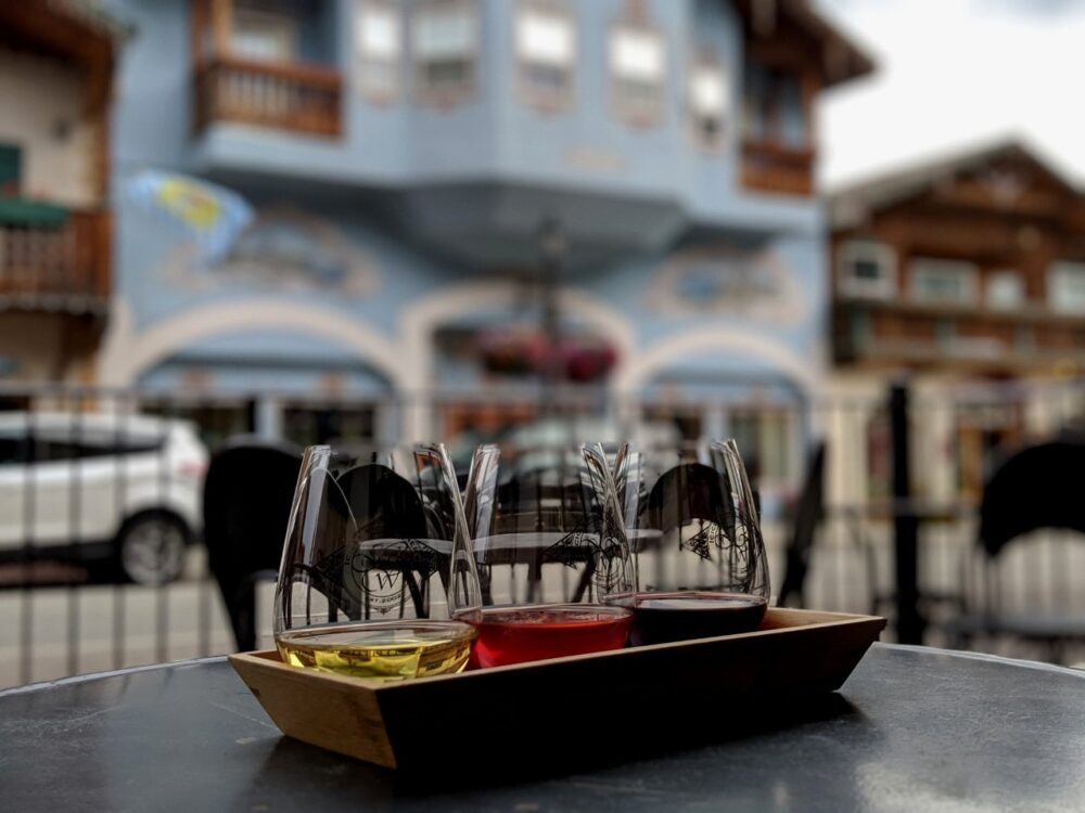 Three glasses of wine in focus in front of Leavenworth Bavarian buildings