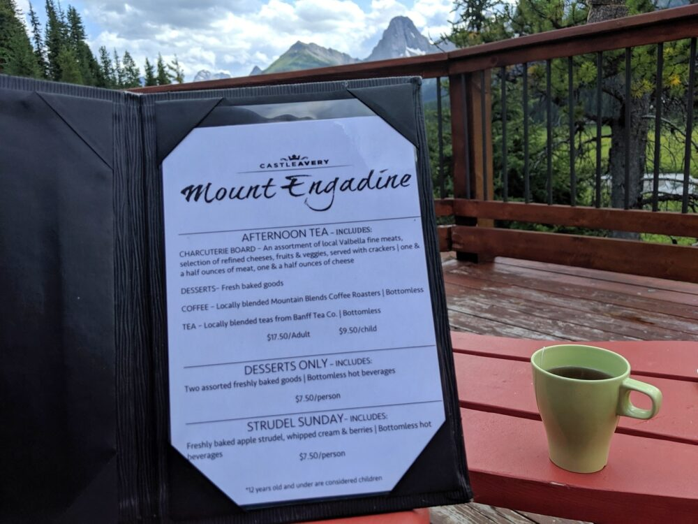 Cup of tea on table, menu held in front and mountain view behind on Mount Engadine Lodge deck